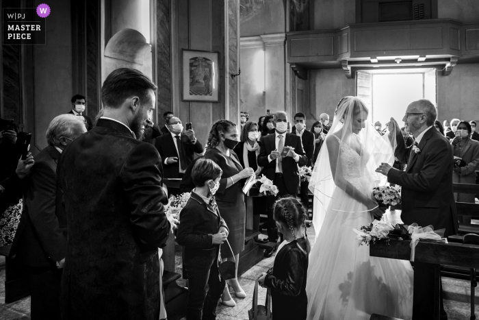 Ceremony wedding photography from an Italy Church of Maccagno - Varese of the Father and brides Symbolic moment