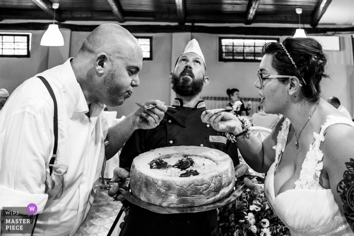A Varese wedding photographer captured this Italy-Novara - Venue: Laghetto della Gelata image of the Bride and groom testing the Risotto