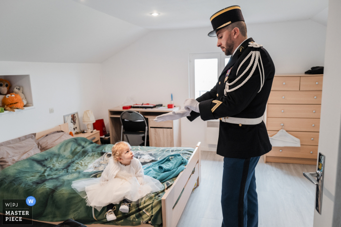 Wedding photography of the military preparations at Home in Chambery as the groom finished getting ready in front of his daughter