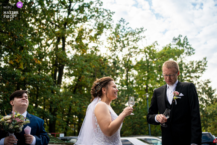 A Prague wedding photographer created this image at a Brno event showing the Traditional welcome drink after arrival to the venue