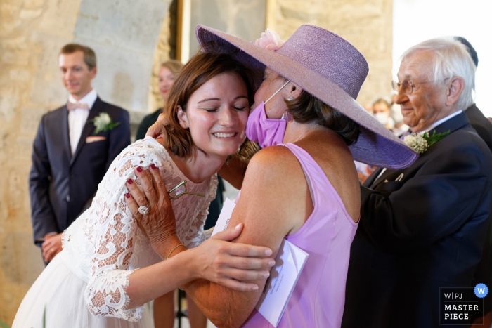 A Toulouse wedding photographer caught this moment on camera at The church of Calvignac in the Lot in Occitanie During the religious ceremony, the bride hugs her mother with great emotion