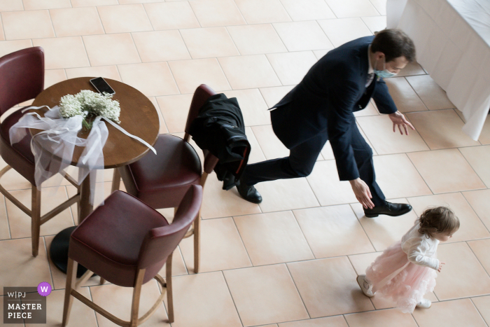 Wedding photography from The Écuries de la Tour in Mondonville in Haute-Garonne in Occitanie - as The little girl runs to escape, Her uncle tries to catch up with her