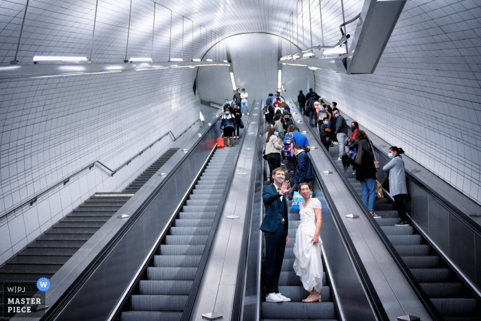 Wedding photography from the Toulouse metro during the Subway exit on the escalator as The groom waves his hand to his guests