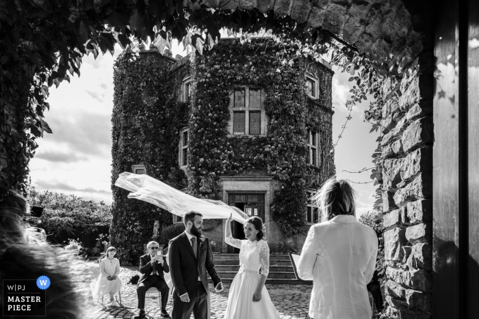 UK wedding reportage photography from Walton Castle, Somerset, England showing the Bride's veil is lifted up by wind during wedding ceremony - Image framed by an arch in the castle walls
