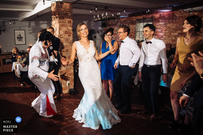 A Lodzkie wedding photographer captured this image at the Best Western Podklasztorze in Sulejow, Poland - Disguised as Elvis, the musician chases the bride during one of the wedding dances