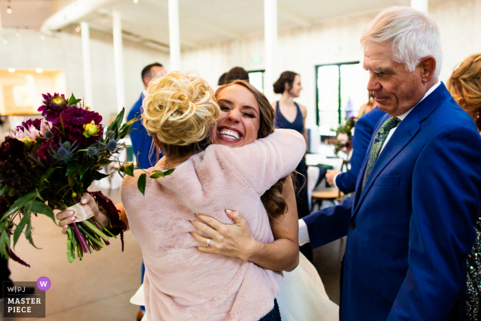 Colorado wedding photography from The Woodlands, Morrison as the bride embraces her new family right after the ceremony