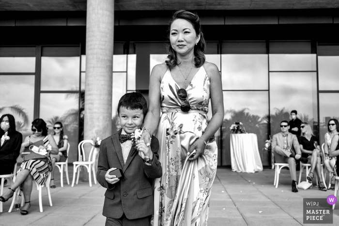 S California wedding photographer captured this image at the Intercontinental Hotel, San Diego, CA of The brides nephew performing his duties as ring bearer