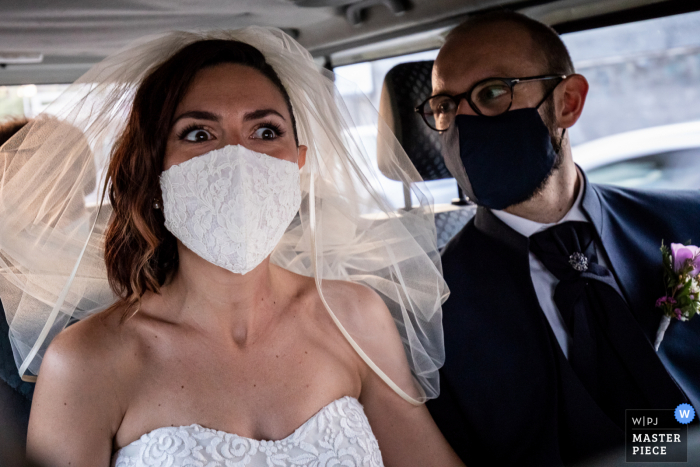 Wedding photography from the car at the Grand Hotel Baia Verde - Aci Castello showing The particular expression of the bride, who has to stay with the mask, while moving with the groom