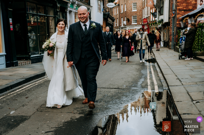 Wedding image of The bride and groom walking happily through the streets of York, with the Cathedral reflected in a puddle