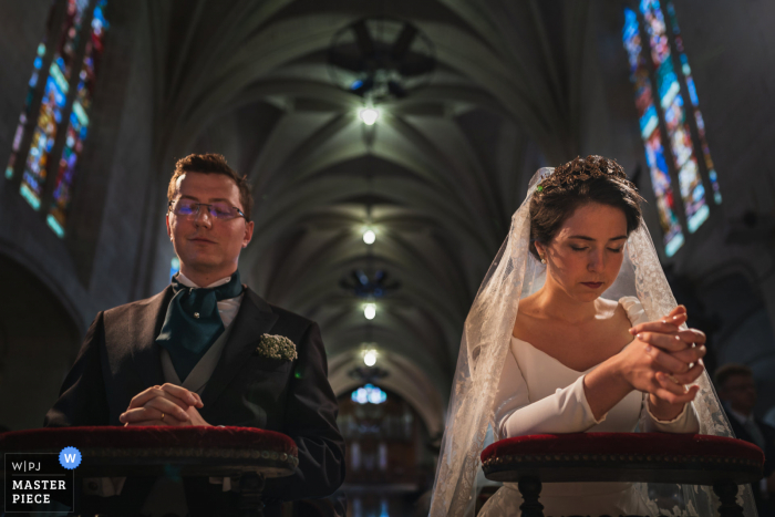A Brittany wedding photographer captured this prayer moment at Brissac-Quincé, France of the Bride and groom during the ceremony