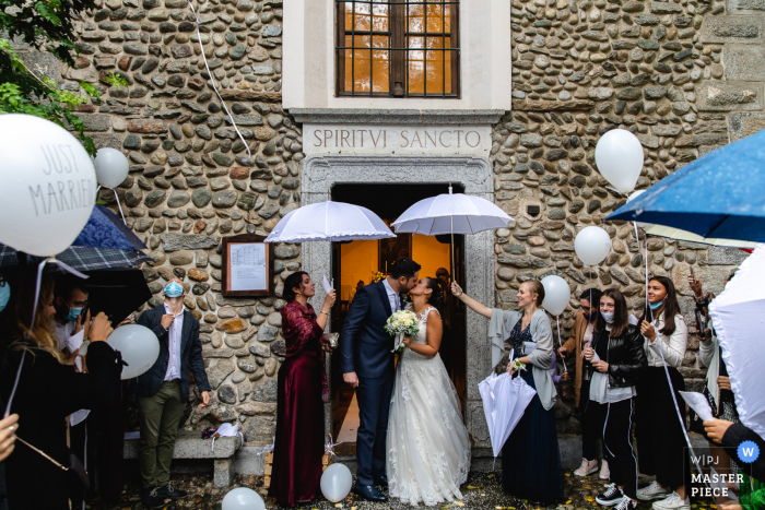 A Verbano-Cusio-Ossola wedding photographer captured this Piedmont Church exit of the couple under umbrellas and balloons