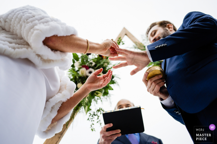 Vermont outdoor wedding photography from Andover, VT showing The bride and groom exchanging rings during the ceremony