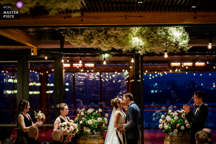 A Virginia wedding photographer captured this District Winery bride and groom first kiss under baby's breath floral clouds