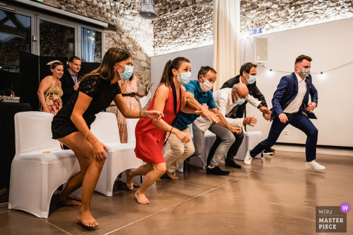 A Paris wedding photographer captured a moment at Domaine de Mauvoisin, Lommoye, France as Guests are running for a game during diner