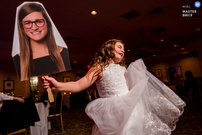 The Belmont Country Club wedding venue image of The flower girl dancing with a cutout of a family member unable to attend the wedding reception party