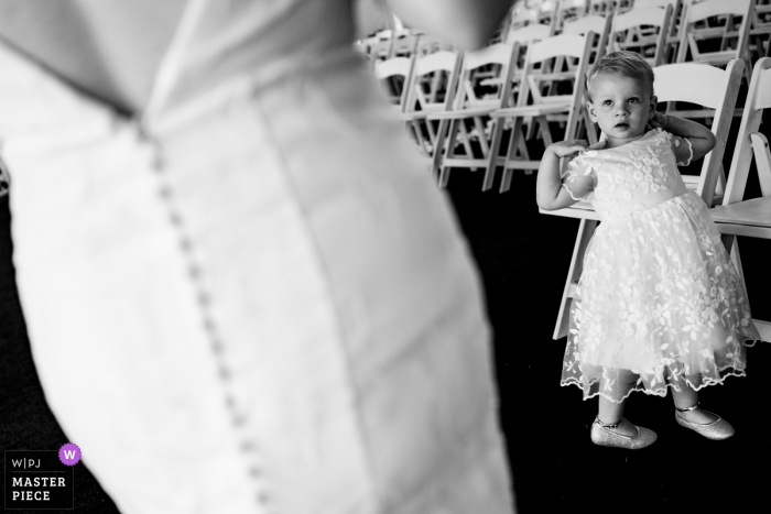Georgia wedding photography from Atlanta of a young girl admiring the bride and her dress at the outdoor ceremony venue