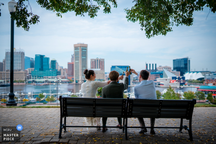 Wedding photography showing The couple and the bride's brother cheers with their mini-champagne in the park overlooking Baltimore's Inner Harbor