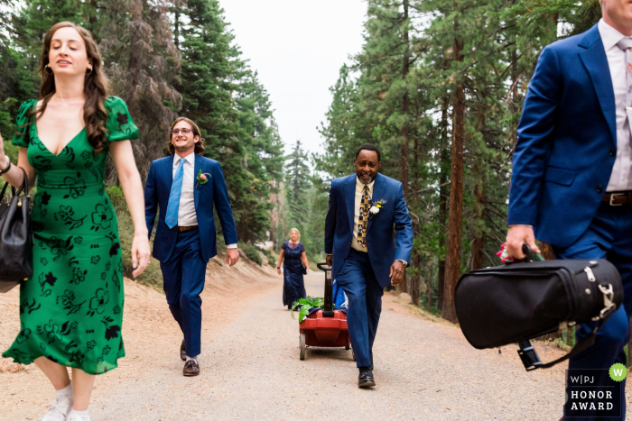 Nevada outdoor wedding photography from Incline Village, NV as the Immediate family members pull a wagon of items up to a mountain lookout in preparation for a covid elopement at Lake Tahoe, NV
