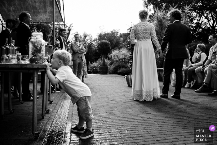 Reportage wedding photography from a reception venue in Amsterdam of a kid drinking water during speech