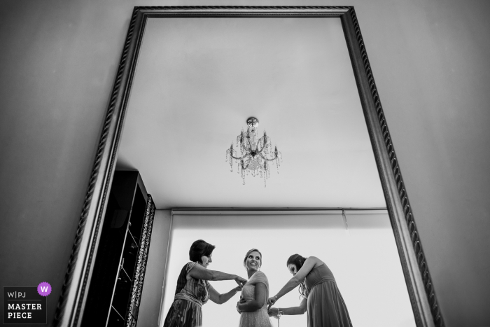 Rio Grande do Sul wedding photographer created this image at Mirage - Porto Alegre of the Bride putting the dress together with her mother and sister