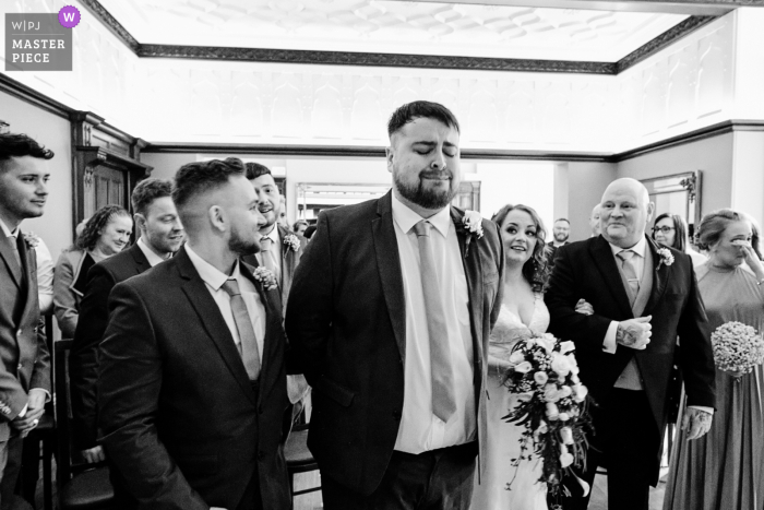 England wedding reportage photographer captured this black and white image at Pendrell Hall showing the Groom overcome with emotion during Bride's entrance