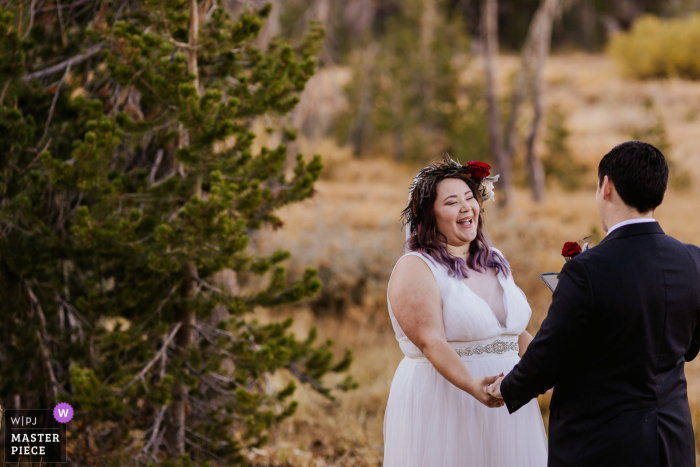 Nevada outdoor, remote wedding photography in New Washoe City, NV showing the The bride giggling, reacting to her fiance's vows