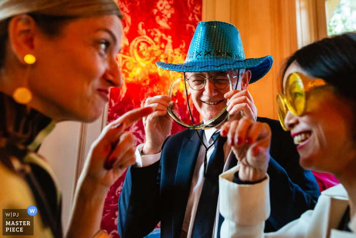 Île-de-France Reception venue Guests playing with photobooth props during wedding dinner in this wedding photo
