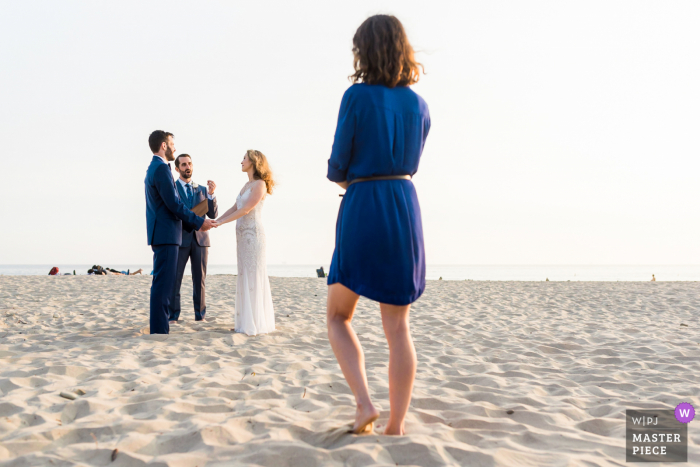 California beach wedding photography from Cupertino, CA	showing A guest looking on as a bride and groom are wed in an intimate beach ceremony