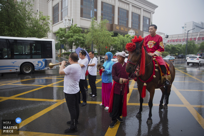 Picture by a Shaanxi wedding photographer of a groom on a horse in the streets during rain