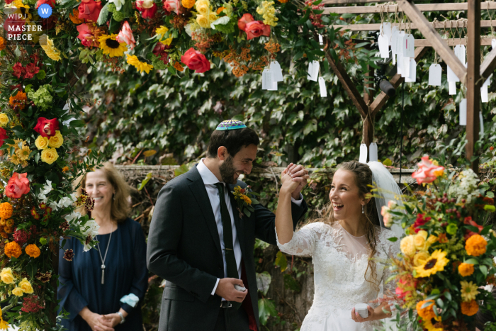 Photo showing a Long Island, NY bride and groom joyfully hold hands and celebrate during their wedding ceremony surrounded by flowers.