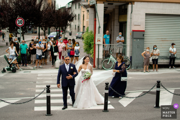 Wedding photography outside the Church of San Andrea, Suisio (Bg) as People on the street watch the bride arrive