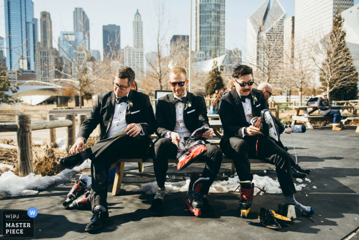 Maggie Daley Park, Chicago Groom & Groomsmen Lacing Up Their Skates in this wedding photo