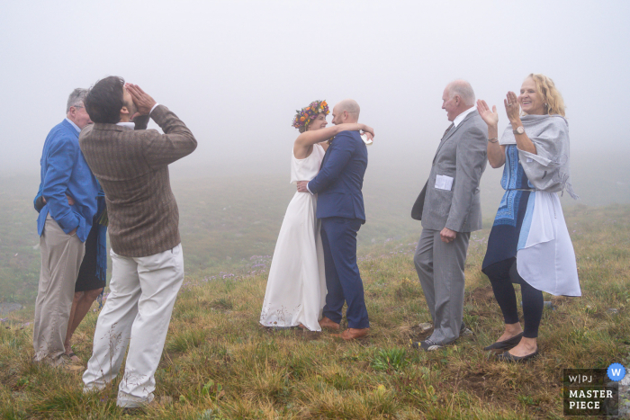Colorado outdoor wedding photography of the Ceremony first kiss in fog