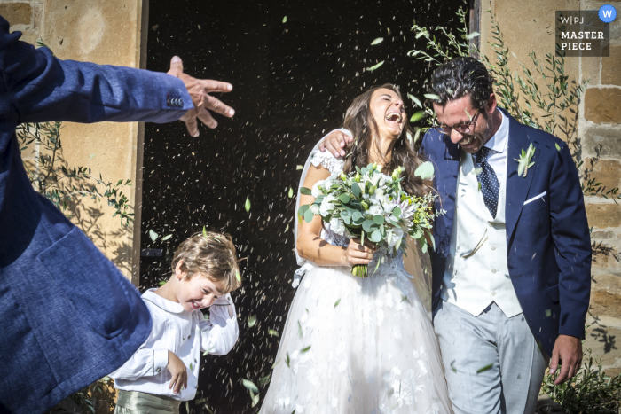 Siena wedding photography at the Church showing confetti flying and much happiness