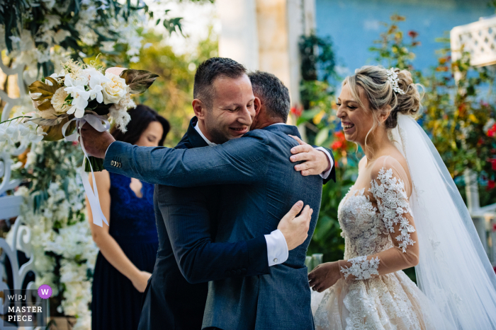 Bulgarian groom and the bride`s father are hugging each other after the ceremony at the Terra Residence, Sofia