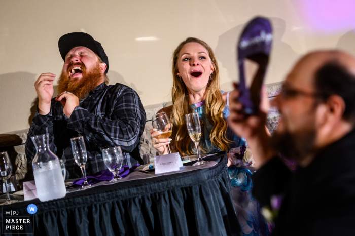 """Wedding Reception venue image from the Tapestry House, Fort Collins, CO showing Wedding guests erupting in laughter as they watch the bride and groom play the """"shoe game"""""""