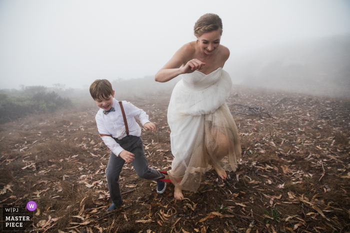 CA wedding photo from Stinson Beach showing the bride and her new son taking part in a three-legged race