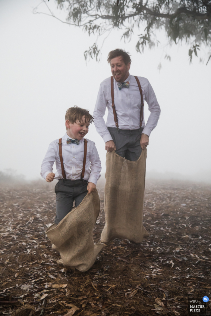 Wedding photo from the cliff edge overlooking the pacific ocean near Stinson Beach, California of a really close potato sack race -- a time honored tradition