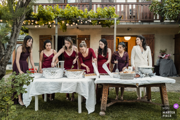 Backyard wedding photo from a Home ceremony venue in Chamberyof the bridesmaids preparing the meal service