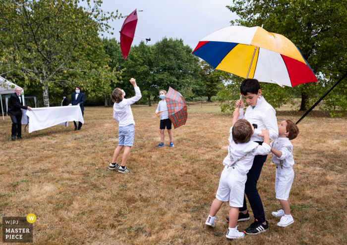 Wedding photography from outdoor event in Cromac - During the cocktail, kids are playing with umbrellas