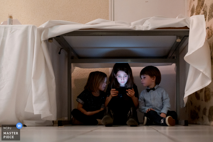 Wedding photo from the reception party at Taysse ponds of Children with ipad during the dinner