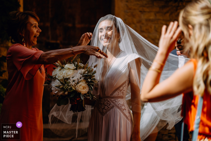 Auvergne-Rhône-Alpes Reception venue image of The bride putting on her veil, her mother laughs with emotion when she finds her