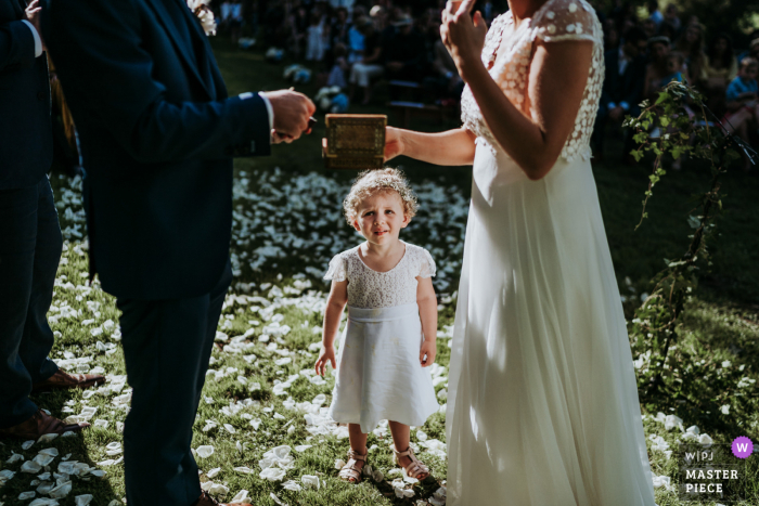 Outdoor, garden wedding photo from Sauveboeuf castle Dordogne France	of A little girl watching her parents get married