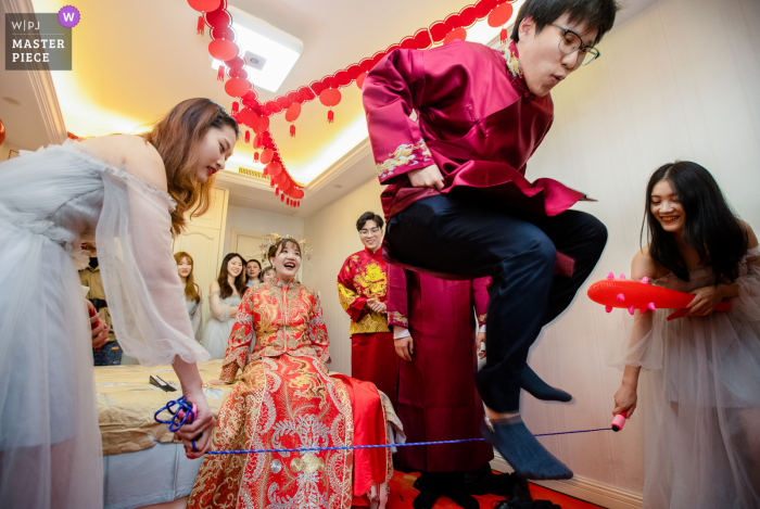 Shaoxing, China groom Plays the game at the door to get the bride in this wedding photo