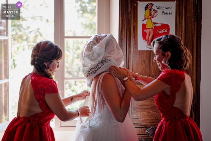 Wedding photo from Domaine de Saint Michel, Giroussens, France as the bride puts on her dress