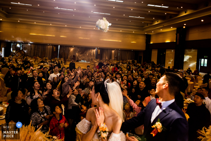 Wedding photography from the Sichuan venue of The bride throwing the flower in her hand, which is a symbol of love and happiness, behind her. Friends of the newlyweds are snatching flowers, and many hands reach high