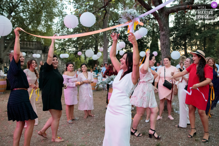 France outdoor wedding photography from Claret village park showing Lots of atmosphere during the ribbon game for the bridal bouquet