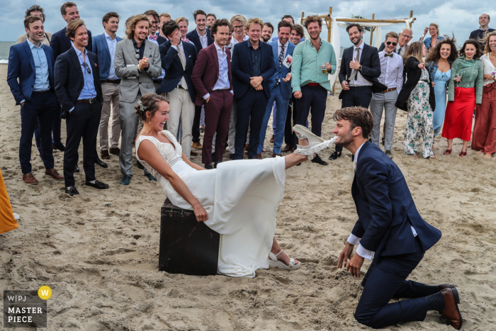 Noord Holland wedding photo from Scheveningen beach of the garter being retrieved by the groom