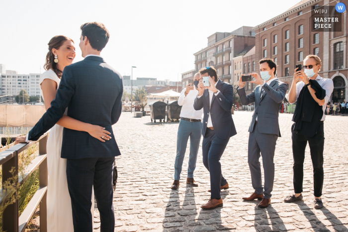 Wedding photo from Flanders - Friends of the bride and groom pose the couple to have a picture of them on their different camera's