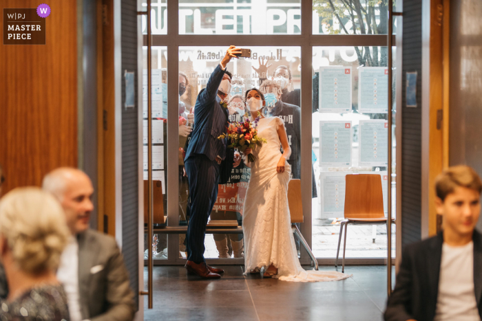Wedding photo from Flanders - bride and groom take a selfie with isolated friends outside the town hall right before the ceremony